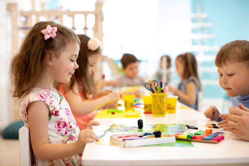 Children group learning arts and crafts in playroom with interest. Kindergarten children group learning arts and crafts in playroom with interest royalty free stock photos