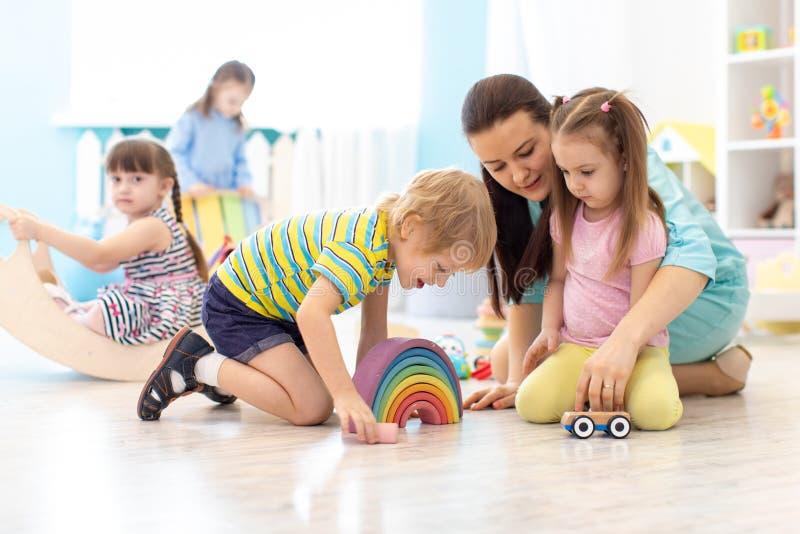 Children group playing in kindergarten. Kids with teacher in classroom stock photos