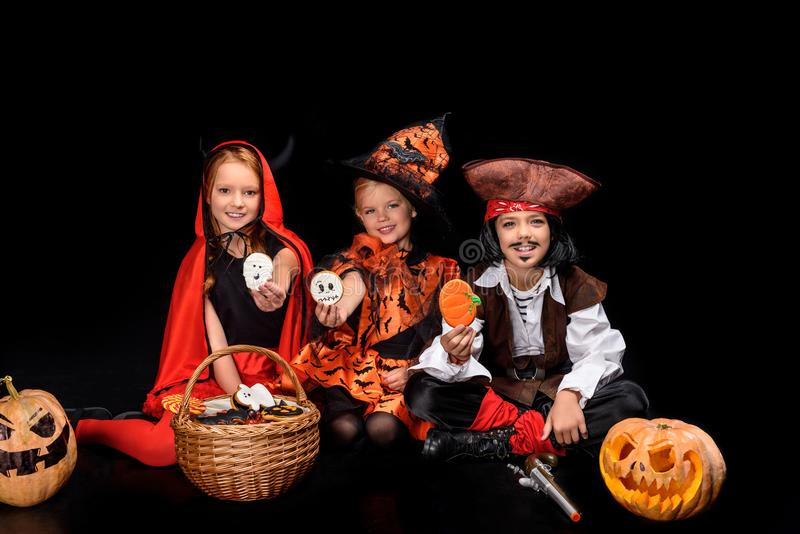 Children in halloween costumes with cookies royalty free stock photos