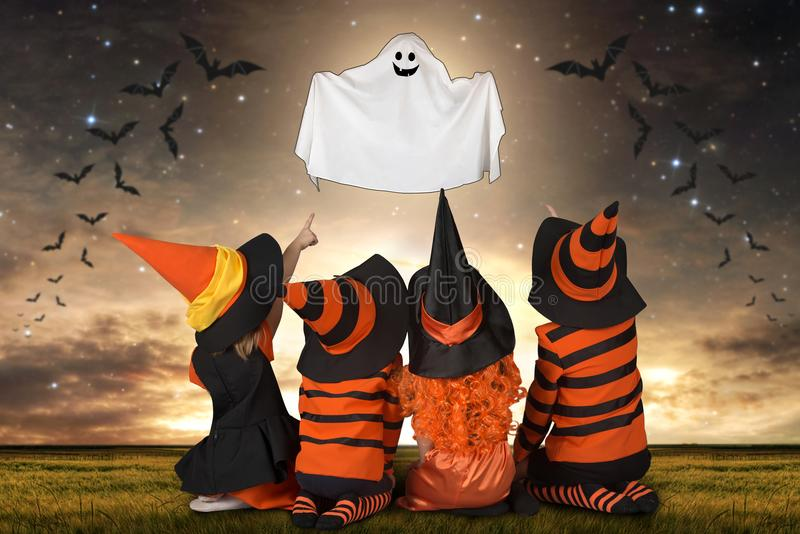 Children in Halloween costumes look at the flying Ghost. royalty free stock photography
