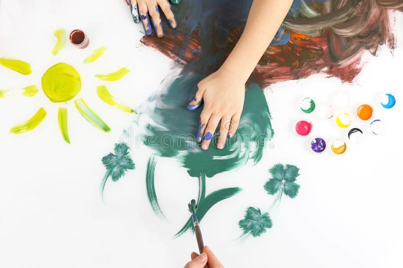 Children hand paint a picture with paints on white background royalty free stock photography