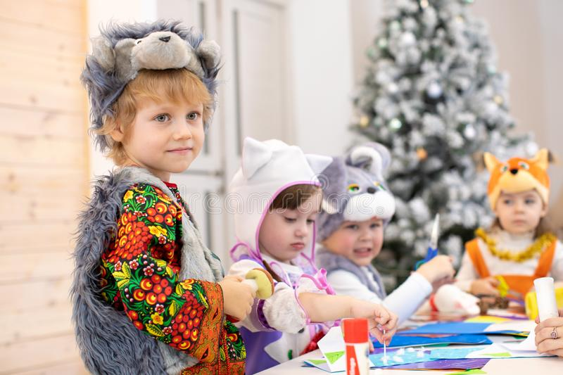 Children handiwork in kids club. Craft lesson in primary school. Kid boy together friends weared animal costumes in stock photography