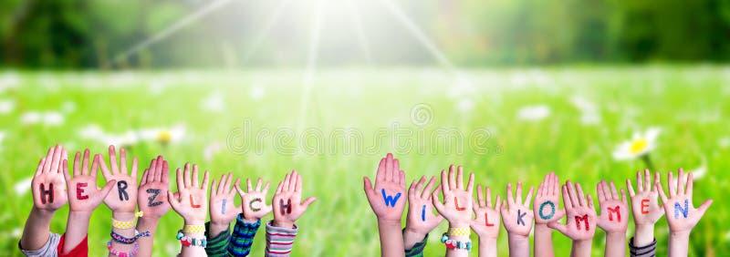 Children Hands Building Word Herzlich Willkommen Mean Welcome, Grass Meadow. Children Hands Building Colorful German Word Herzlich Willkommen Mean Welcome. Green stock images