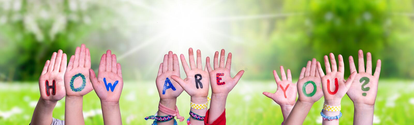 Children Hands Building Word How Are You, Grass Meadow. Children Hands Building Colorful English Word How Are You. Sunny Green Grass Meadow As Background stock image