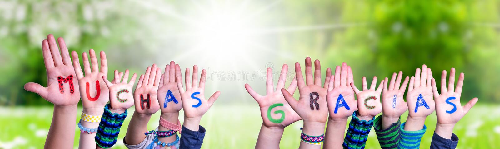 Children Hands Building Word Muchas Gracias Means Thank You, Grass Meadow. Children Hands Building Colorful Spanish Word Muchas Gracias Means Thank You. Sunny royalty free stock photography