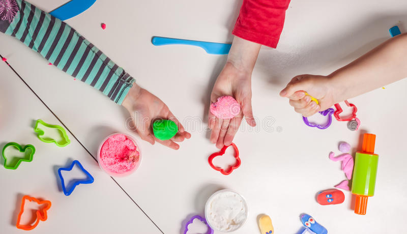 Children hands playing with plasticine royalty free stock images