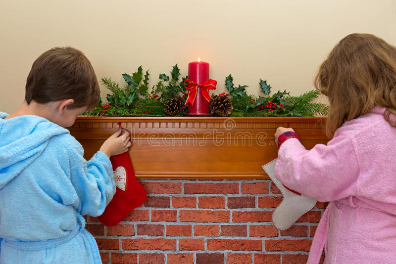 Children hanging stockings over the fireplace royalty free stock images