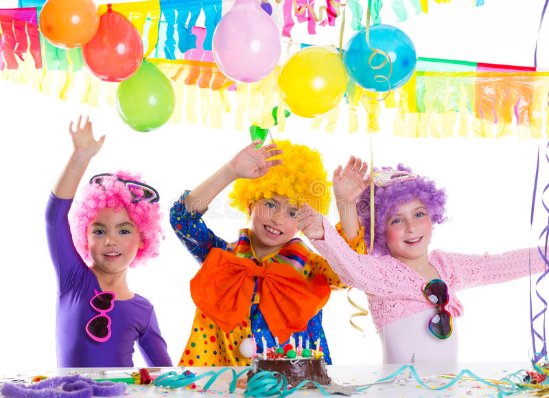 Children happy birthday party with clown wigs. And chocolate cake stock photography