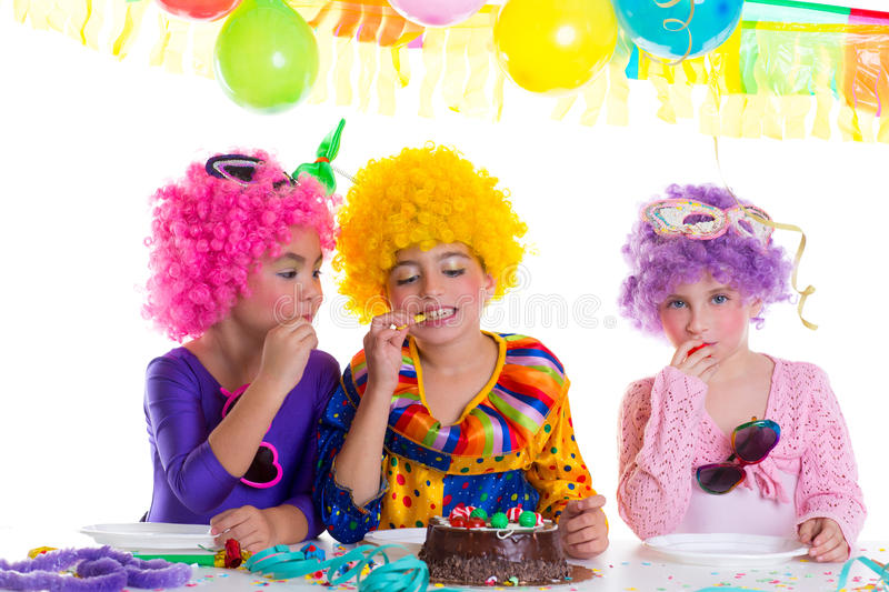 Children happy birthday party eating chocolate cake. With clown wigs royalty free stock photos