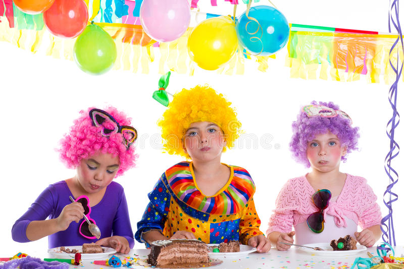 Children happy birthday party eating chocolate cake. With clown wigs royalty free stock photography