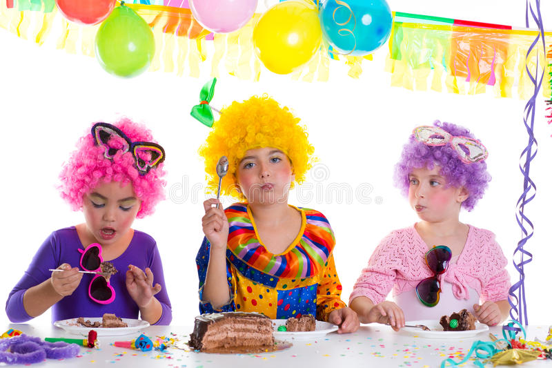 Children happy birthday party eating chocolate cake. With clown wigs stock photo