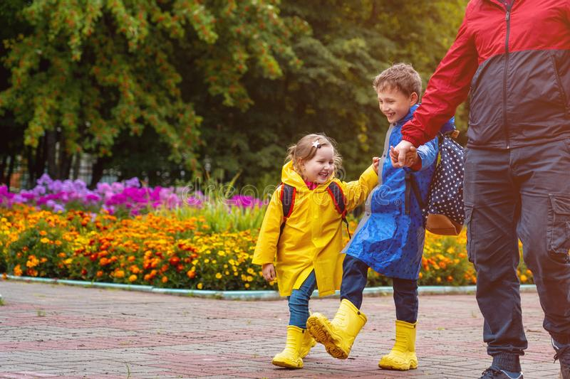 Children happy with joy laugh go to school, dressed in raincoats, with a briefcase behind the backpack. Dad accompanies his daughter and son in rainy weather royalty free stock photography