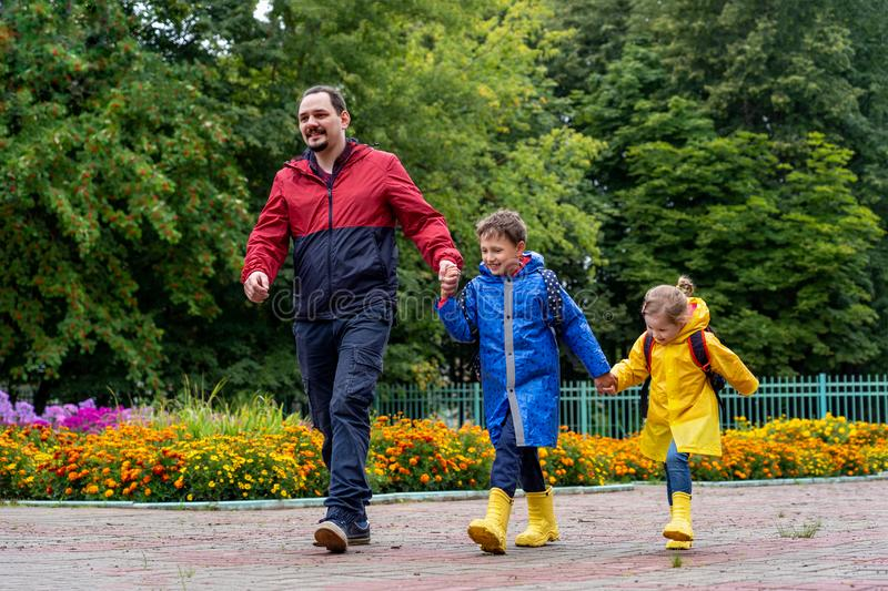 Children happy with joy laugh go to school, dressed in raincoats, with a briefcase behind the backpack. Dad leads his daughter and son daroga to school in stock photo