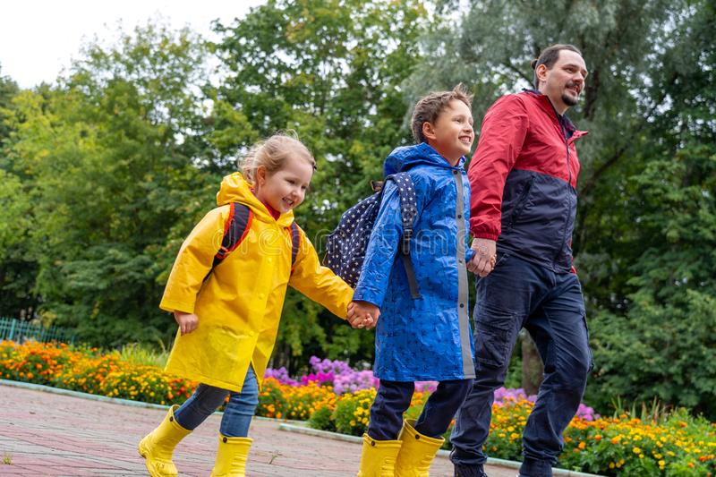 Children happy with joy laugh go to school, dressed in raincoats, with a briefcase behind the backpack. Dad leads his daughter and son daroga to school in stock photography
