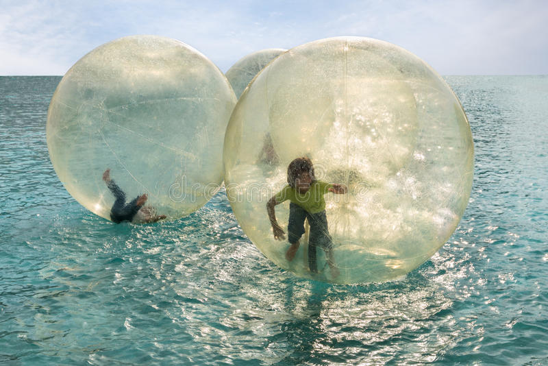 Children have fun inside plastic balloons on the sea stock photo