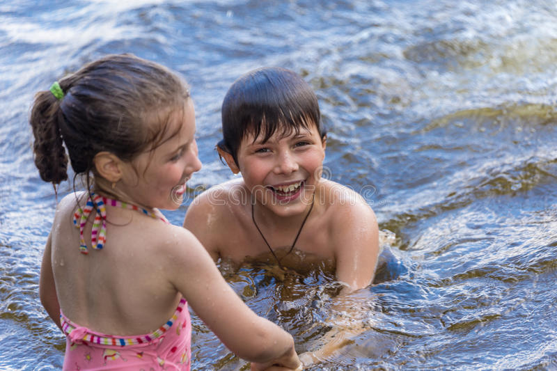 Children have fun in a lake royalty free stock image
