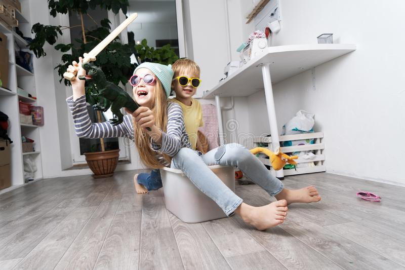 Children have fun and ride in a white plastic box. The room is a mess. Lifestyle portrait royalty free stock image