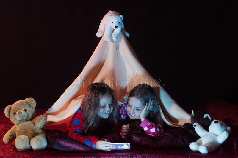 Children have pajama party with teddy bears. Girls with smiling. Faces lie under blanket on black background. Childhood and pajama party concept. Kids in stock image