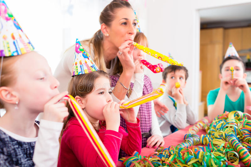 Children having birthday party with fun. Blowing streamers, group of kids with mother royalty free stock photography