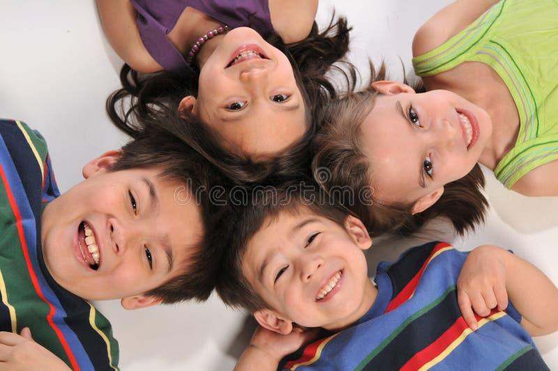 Children having fun. Portraits of children lying down on the floor ans smiling stock images