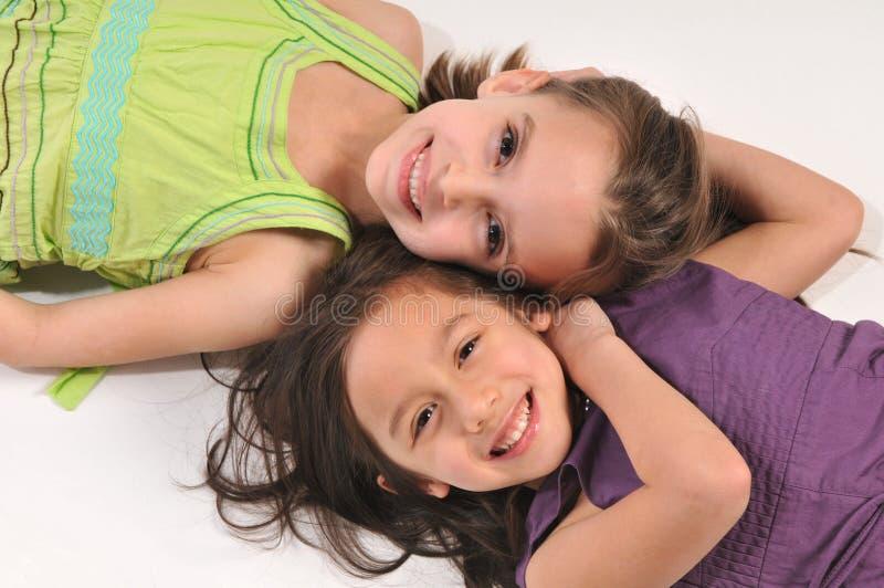 Children having fun. Portraits of children lying down on the floor ans smiling stock photos