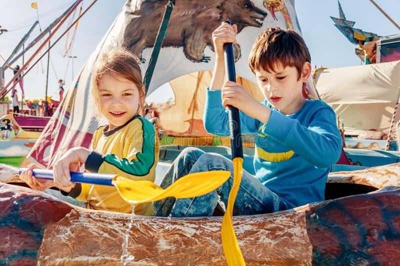 Children having fun at amusement park. Ride on canoe. Happy childhood concept. Children having fun at amusement park. Ride on canoe stock photo