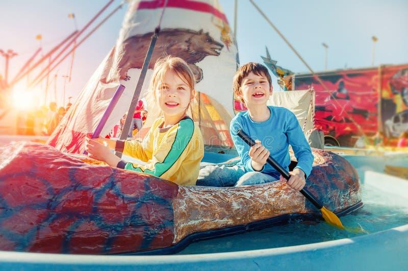 Children having fun at amusement park. Ride on canoe. Happy childhood concept. Children having fun at amusement park. Ride on canoe stock image