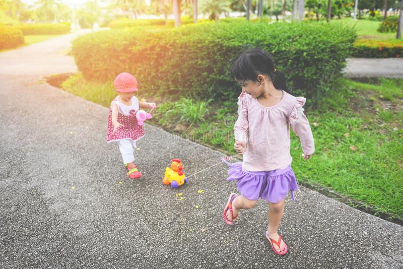 Children having fun playing outside Asian kids girl running happy with toys in the garden park - International Children's Day royalty free stock photos