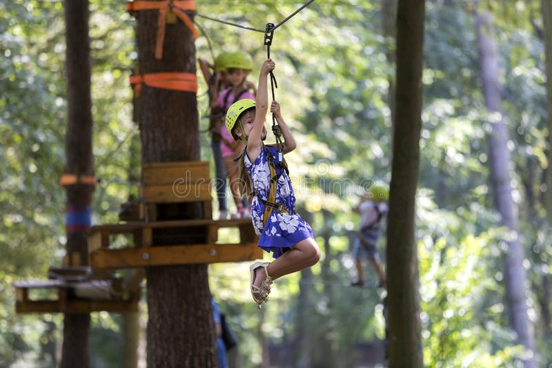 Children having fun on rope way in recreation park. Cute young g royalty free stock photos