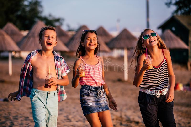 Children having fun while walking along a sandy beach royalty free stock photo