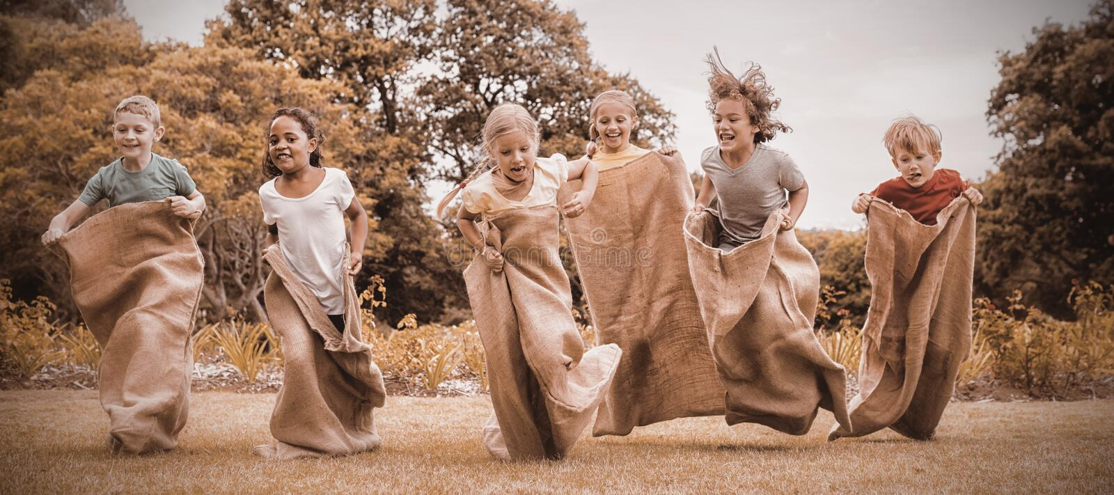 Children having a sack race in park stock photos