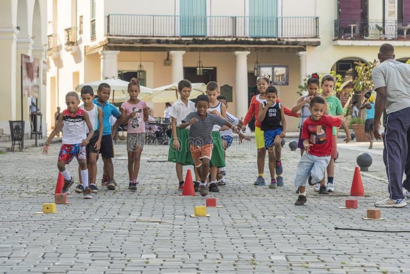 Children having sports lesson Havana. Children having sports lesson with relays on Plaza Vieja in Old Havana, Cuba royalty free stock images