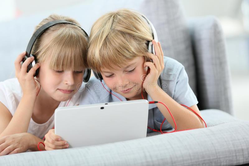 Children with headphones listening to music. Kids listening to music on internet with tablet stock images