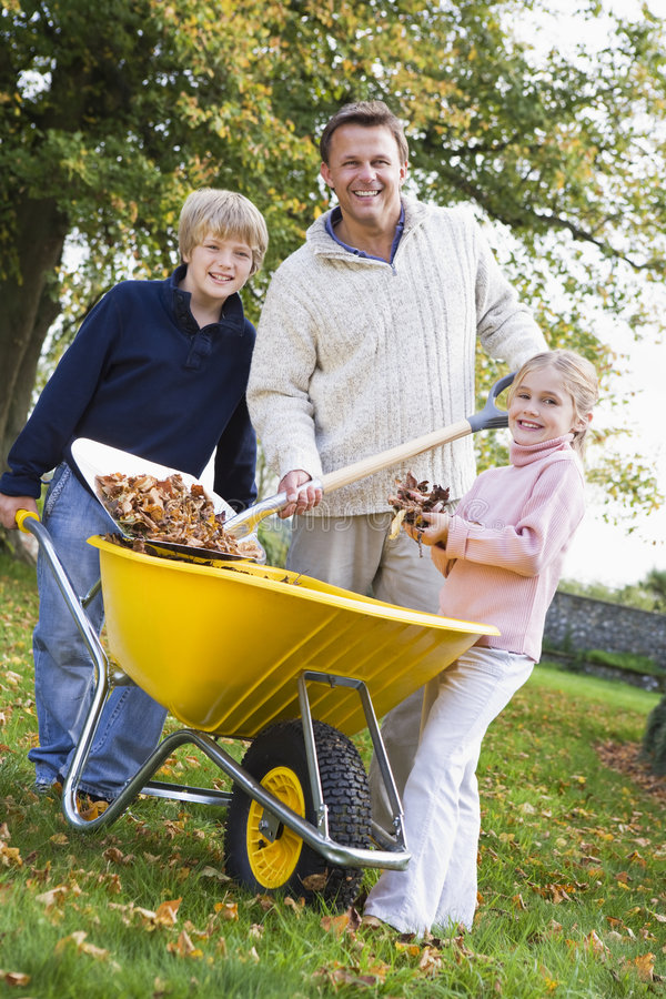 Children helping father to collect autumn leaves royalty free stock photos