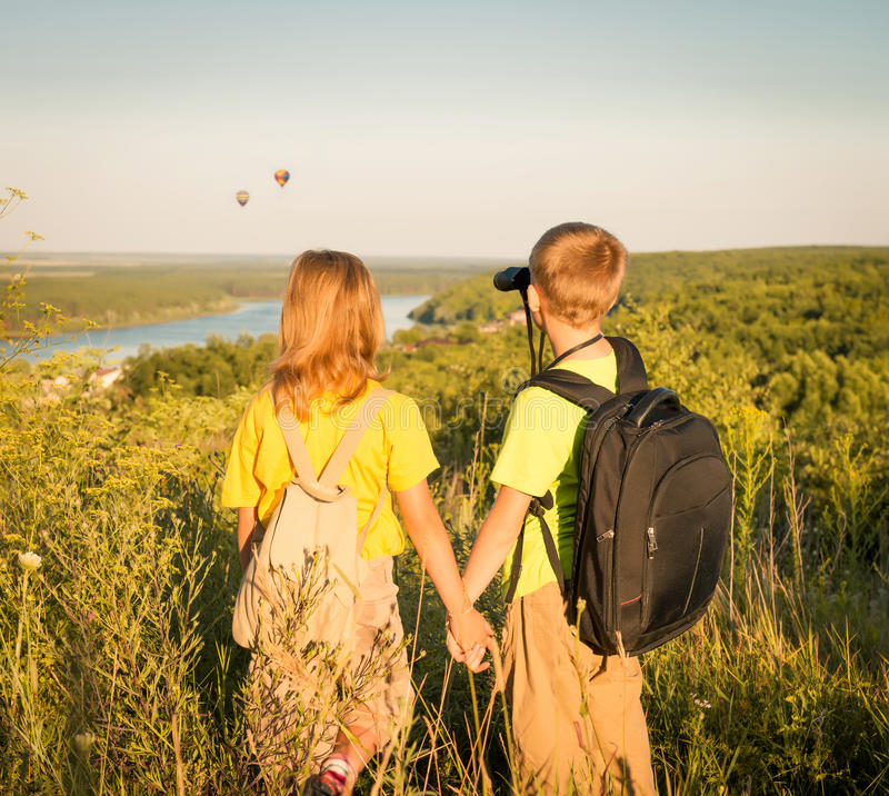 Children hiking.Girl and boy looking through the binoculars on h stock images