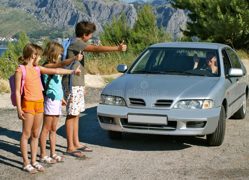 Children hitchhiking. Brother and sister - three children - best friends hitch a woman in a silver car. Horizontal photo royalty free stock image