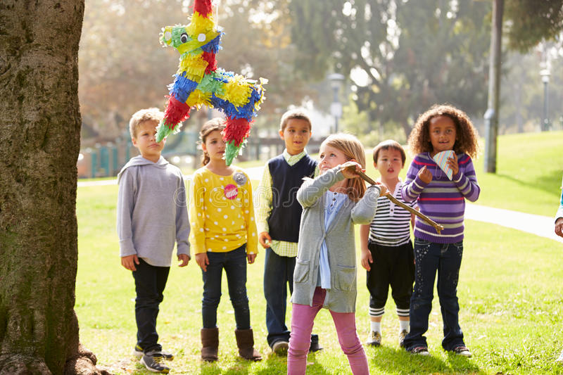 Children Hitting Pinata At Birthday Party stock images