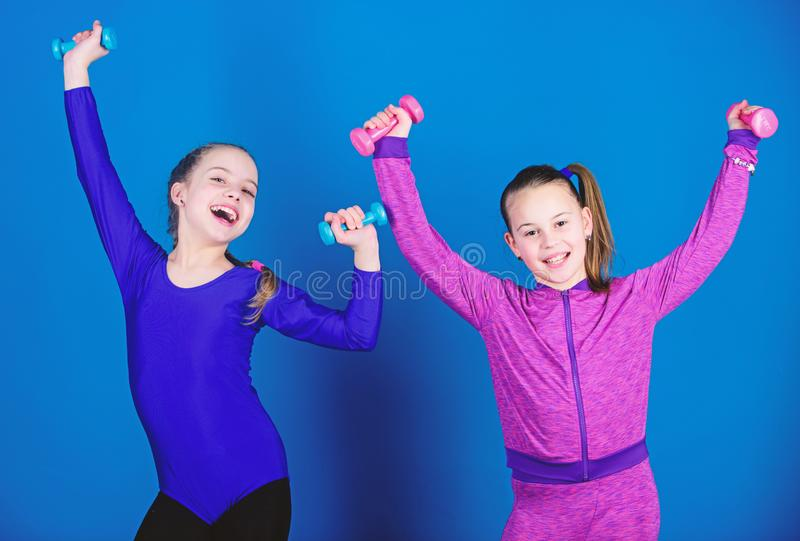 Children hold dumbbells blue background. Sport for teens. Easy exercises with dumbbell. Sporty upbringing. On way to. Stronger body. Girls exercising with stock photography