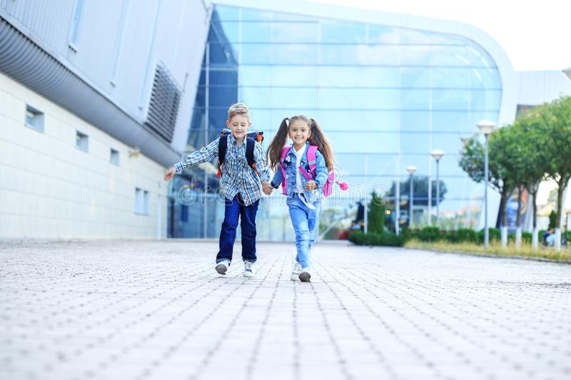 Children hold hands and run. Schoolchildren with backpacks. The concept of childhood, family, education. And school stock photography