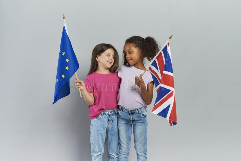 Children holding British and European Union flags. Girls embracing and holding British and European Union flags royalty free stock image