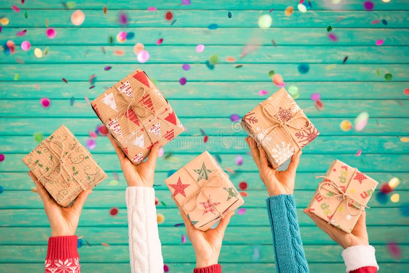 Children holding Christmas gift boxes. Kids hands against confetti falling background. Xmas holiday concept stock images