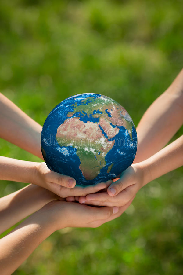 Children holding Earth planet in hands royalty free stock image