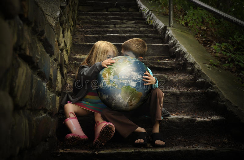 Children Holding Earth Planetin Secret. Children are holding the planet earth on wet dark stairs for a weather or season concept about the environment stock photography
