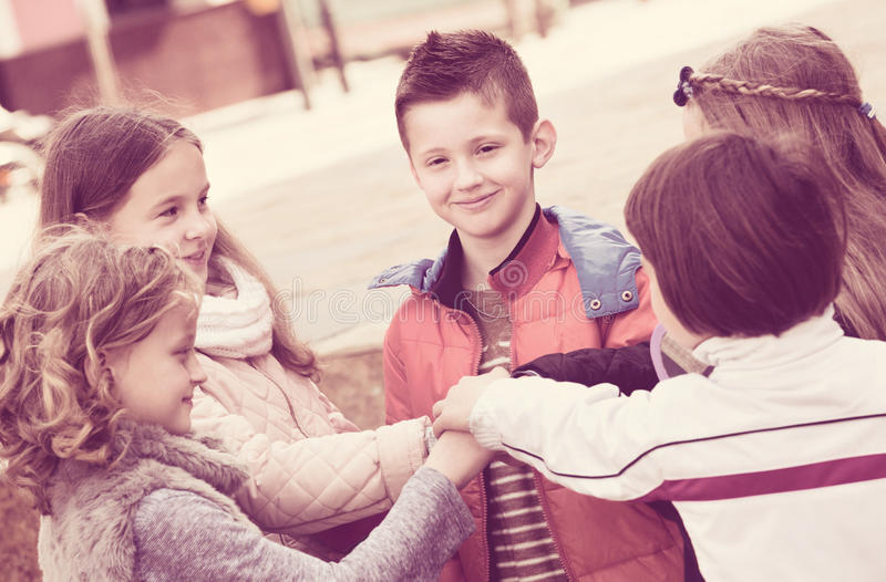 Children holding hands and giving friendship vow. Positive happy smiling children holding hands and giving friendship vow stock photos