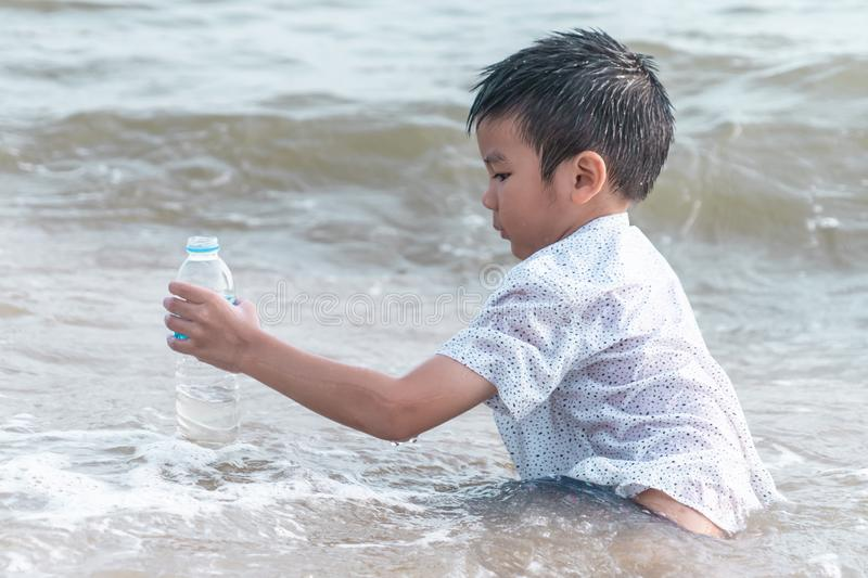 Children holding Plastic bottle that he found on the beach for enviromental clean up concept. Children is holding Plastic bottle that he found on the beach for stock image