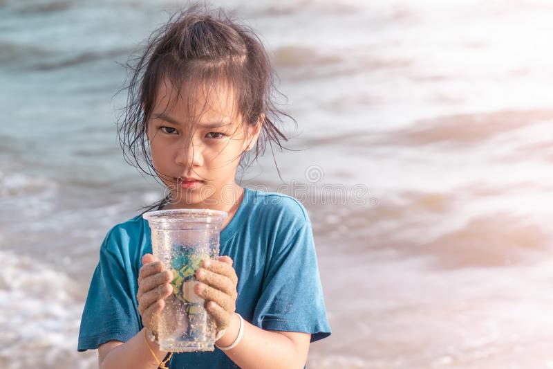 Children holding Plastic cup that he found on the beach for enviromental clean up concept. Children is holding Plastic cup that he found on the beach for stock photo