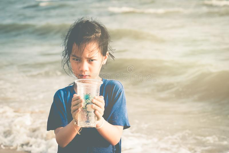 Children holding Plastic cup that he found on the beach for enviromental clean up concept. Children is holding Plastic cup that he found on the beach for stock photos