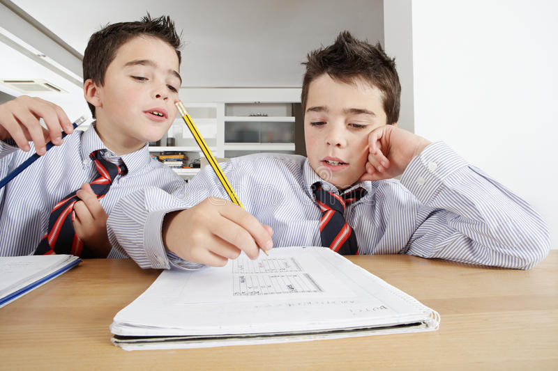 Children with Homework at Home. Two young twin brothers doing homework at home, sharing a wood table stock photos