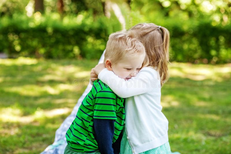Children hug in the garden. 2-3 years. Girl and boy. The concept stock image