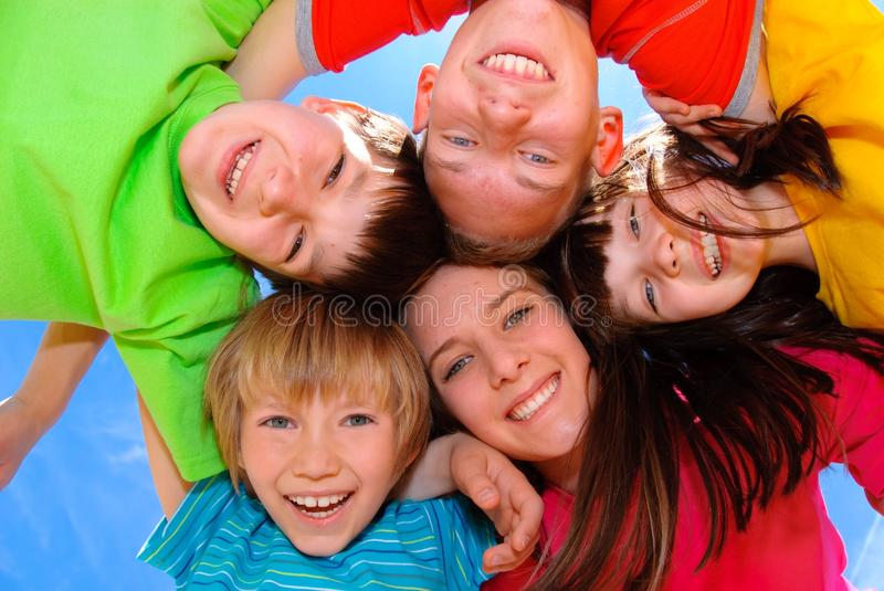 Children hugging. Happy children hugging in a circle against blue sky